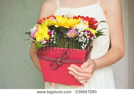 Girl Holding A Box Of Multicolored Flowers.