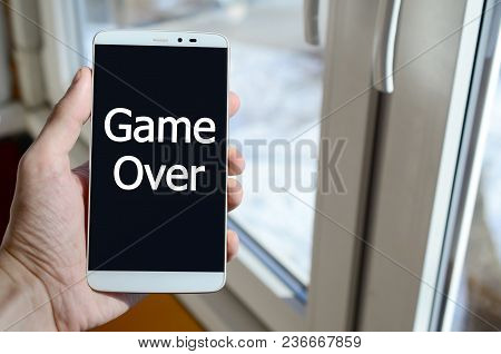 A Person Sees A White Inscription On A Black Smartphone Display That Holds In His Hand. Game Over