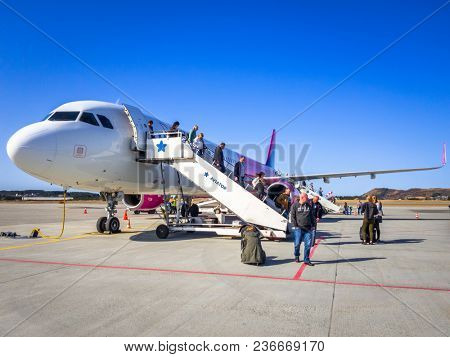 Alesund, Norway - April 13, 2018: People getting off Wizz air plane on Alesund Vigra Airport in Norway. Wizz air is a low-cost airline with largest fleet in Hungary who serves over 30 countries.