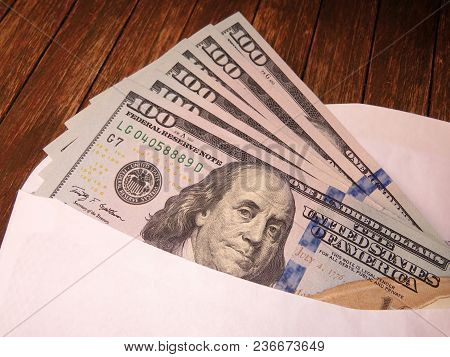 Us Dollars In White Envelope On The Wooden Table. Income, Bonus Or Bribe Concept