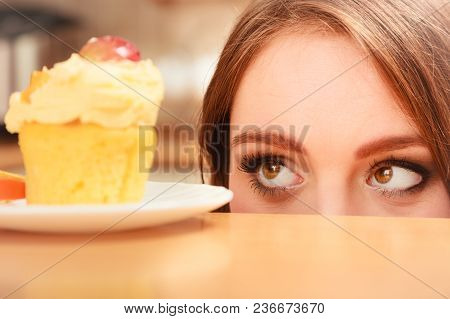 Woman Looking At Delicious Cake With Sweet Cream And Fruits On Top. Appetite And Gluttony Concept.