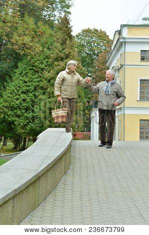 Portrait Of Beautiful Caucasian Senior Couple Walking  In City Park
