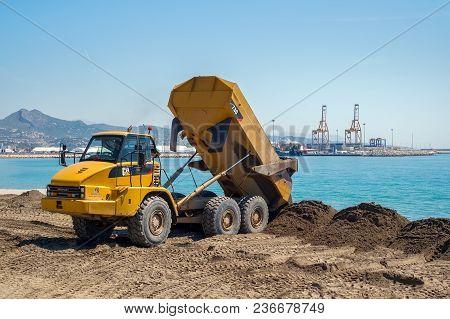 Malaga, Spain - April 17, 2018. Large Trucks Restore Sand On The Coast Expanding The Beach Huelin, M