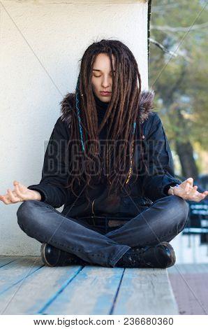 Girl With Dreadlocks Meditation On The Street