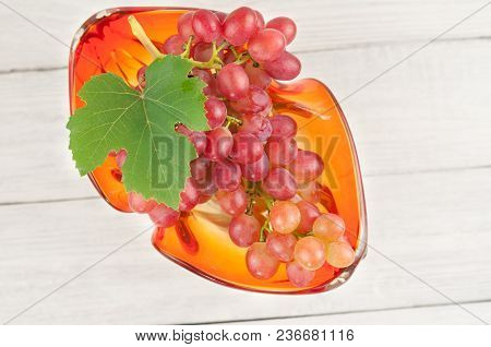 Bunch Of Fresh Ripe Pink Grapes With Green Leaf In Glass Vase On Old Wooden Rustic White Planks