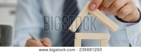Male Hand Holds The Roof To The Lock In The Hand Against The Backdrop Of The Toy House Sale Purchase