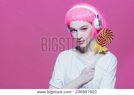 Trendy girl with pink hair wearing headphones is eating lollipop. Pink background. Youth style, leisure.