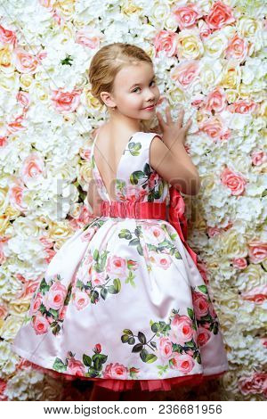 Portrait of a cute little girl in a beautiful summer dress posing on a background of roses. Kid's fashion, style.