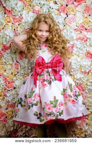Portrait of a cute little girl in a beautiful summer dress with blonde curly hair. Background of roses. Kid's fashion, style.