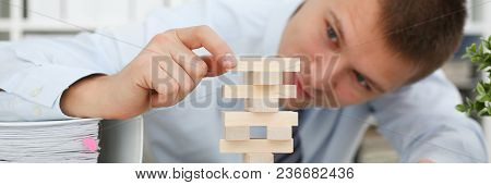 Businessman Plays In Strategy Hand Rearranging Wooden Blocks Involved During Break At Work In Office