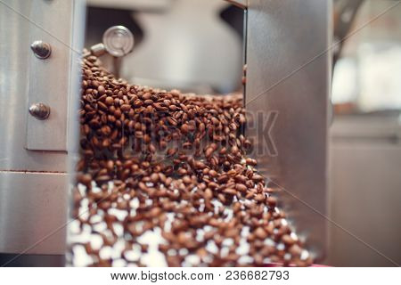Image of falling roasted coffee beans from roaster
