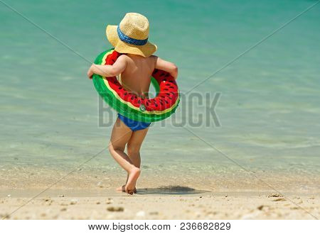 Two year old toddler boy with inflatable swim ring on beach