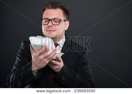 Portrait Of Business Man Smelling Lunch Box.