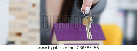 Female Hand Holds The Key To The Lock In The Hand Against The Backdrop Of The Toy House Sale Purchas