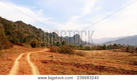 Dirt Road Winds Between Arid Farmland And Low Mountain Range In Shan State, Myanmar