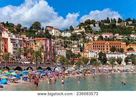 MENTON, FRANCE - AUGUST 15, 2014: People on public beach as old colorful houses on background in Menton - small town on French Riviera, famous destination and popular tourist resort.