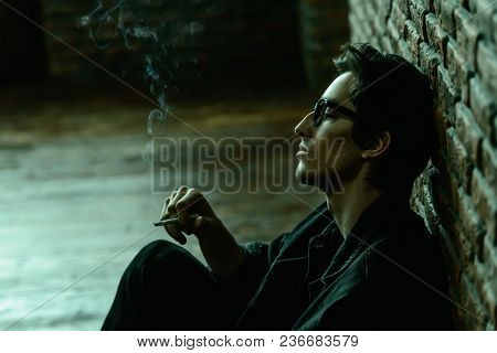 Attractive young man thoughtfully and calmly smoking a cigarette. Loft style interior. Men's beauty, fashion. Optics style.
