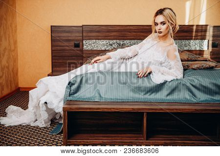 Magnificent young woman posing in bedroom dressed in evening or wedding white dress. Beauty, fashion.