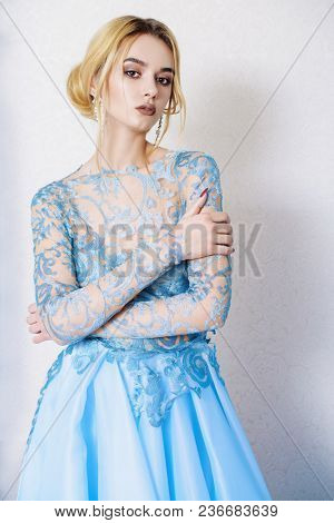 Portrait of a beautiful young woman in elegant blue dress. Luxurious apartments. Beauty, fashion.