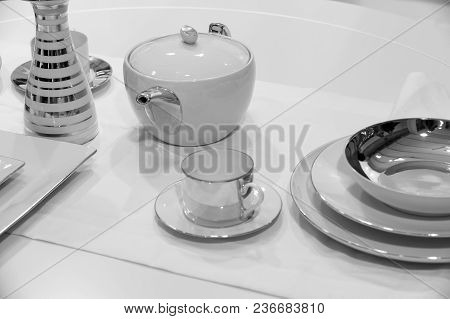 Tea service or set with pot, cup, saucer, plates and vase with golden gilt served on white table cloth background. Tea party or ceremony concept poster