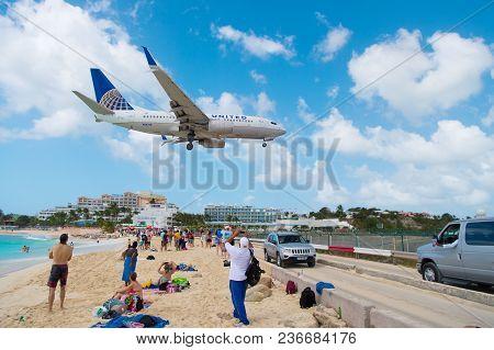 Philipsburg, Sint Maarten - February 13, 2016: Airplane Land Over People On Maho Beach. Plane Low Fl