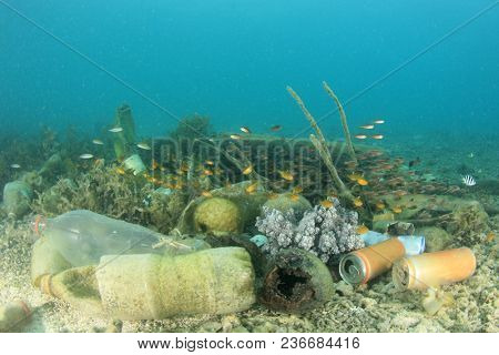 Underwater pollution in ocean problem. Bottles, bags and cans on coral reef