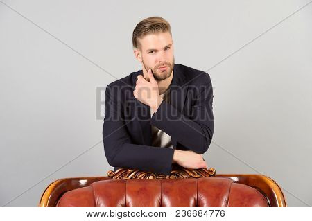 Businessman Touch Beard With Hand. Bearded Man Stand At Chair. Macho With Stylish Hair In Formal Sui