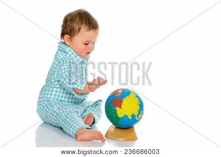 A Cute Little Boy Is Playing With A Globe. The Concept Of Child Development In The Family, Education