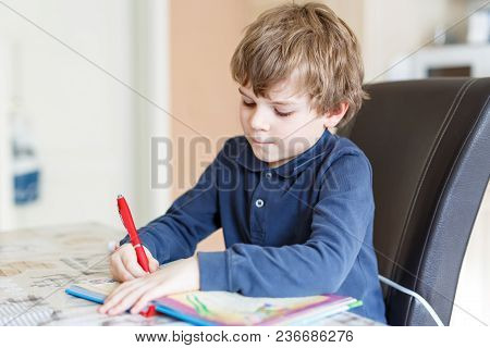 Cute Little Preschool Kid Boy At Home Making Homework, Writing Letters With Colorful Pens. Little Ch