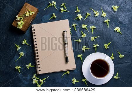 Cup Of Coffee, Notebook, A Wooden Box And Flowers On A Dark Blue Background. The Concept Of The Star