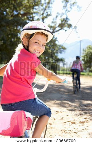 Little girl on country bike ride with mom