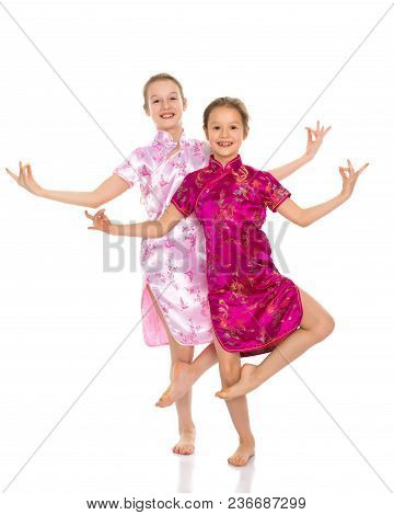Lovely Little Girls In Chinese National Dresses. The Concept Of A Happy Childhood, Style And Fashion