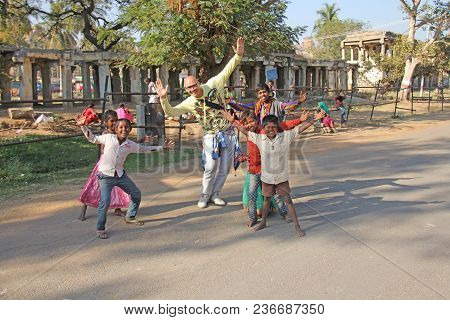 India, Hampi, 02 February 2018. A Bald And Cheerful European Man Dances With Children From India. Jo