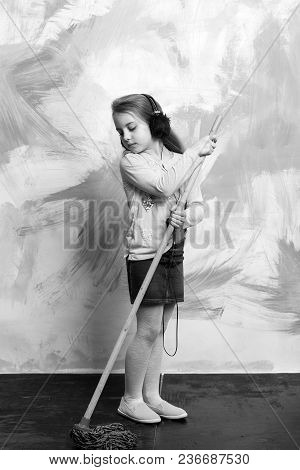Cleaning And Purity. Housekeeper Kid In Earphones. Child Cleaner With Broom On Colorful Background.