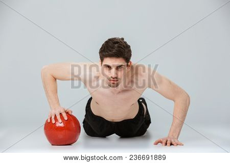 Portrait of a serious young half naked sportsman doing push ups with a heavy ball isolated over gray background