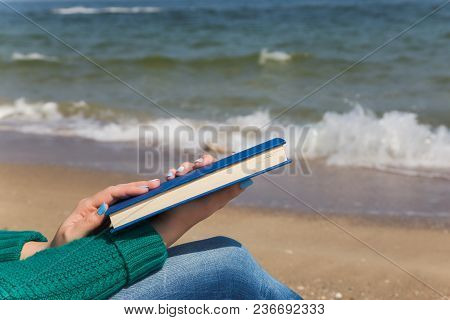 Closeup View Of Two White Female Hands Holding Thick Blue Book. Woman Reading At Sea Beach On Sunny
