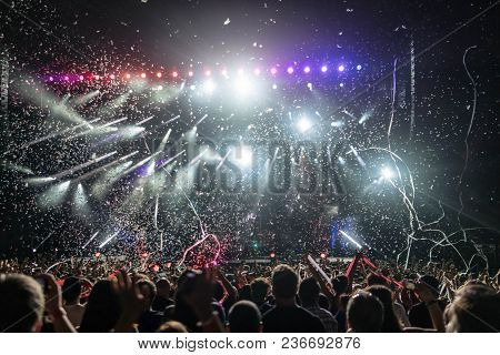 Silhouettes Of People At The Concert In Front Of The Bright Lights Of The Stage. Dark Background, Co