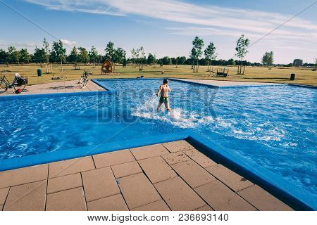Boy Swimming In A Street Pool On A Sunny Summer Day. Rare View. Copy Space.