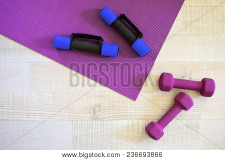 Violet Yoga Mat And Four Sport Dumbbells On Light Wood Textured Floor Background With Empty Space Fo