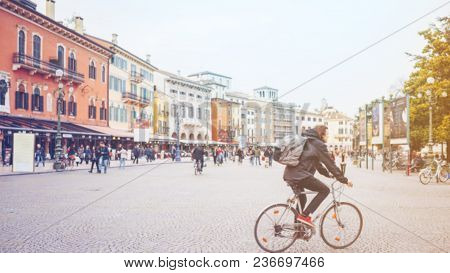 Man Riding A Bike And Crowd Of People Walking In The City Square, Blurred Backgound.