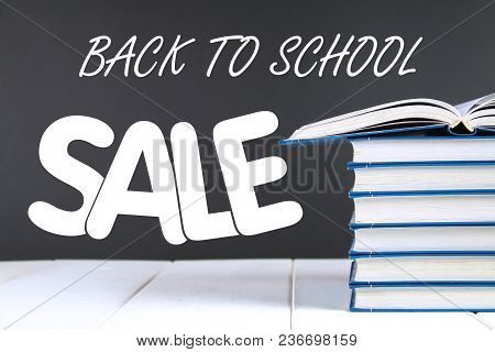 A Stack Of Books On A Chalkboard Background. One Hidden Book On Top Of The Pile. Sale