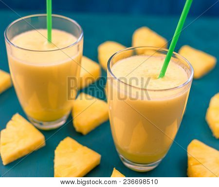 Pineapple Juice Poured In A Glass And Pineapple Fruits Around