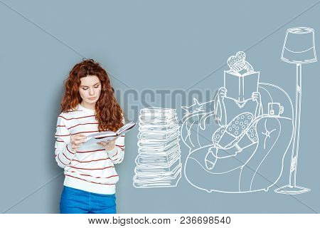 Cozy Evening. Clever Calm Student Standing With A Book In Her Hands And Looking Concentrated On Read