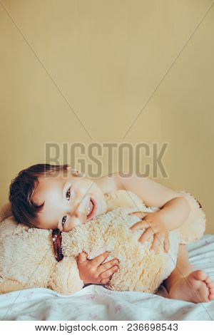 Cute Baby Boy With Teddy Bear In Bedroom. Newborn Child Smiling And Relaxing In Bed. Nursery For You