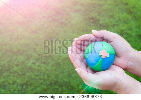 World Earth Day April 22 Concept. Woman Hand Holding Handmade Globe On Green Grass Field Background.