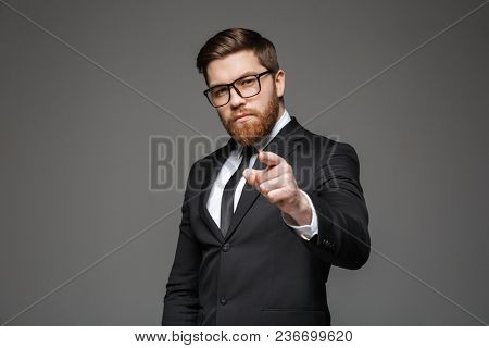 Portrait of a confident young businessman dressed in suit pointing finger at camera isolated over gray background