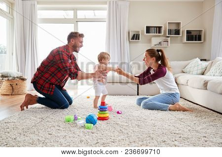 Toddler girl walking from dad to mum in sitting room