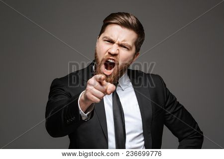 Portrait of a furious young businessman dressed in suit pointing finger at camera isolated over gray background