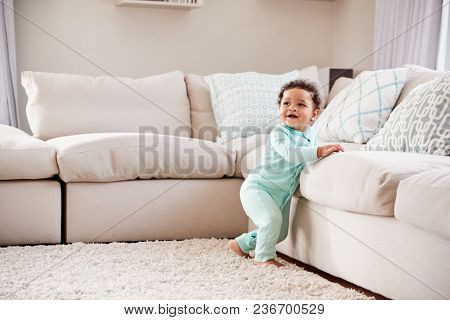 Happy mixed race toddler boy playing in sitting room