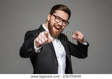 Portrait of a happy young businessman dressed in suit pointing fingers at camera isolated over gray background